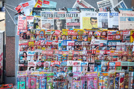 VIENNA, AUSTRIA - NOVEMBER 6, 2019: Magazine rack shelves filled with journals and newspaper in German, from an Austrian press reseller in downtown Vienna.Picture of a press kiosk in the center of Vienna, Austria, filled with newspapers aligned in a mag