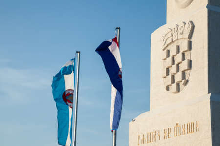 VUKOVAR, CROATIA - MAY 11, 2018: Croatian coat of arms, called grb republike hrvatske, with a mention of the country in ancient croatian alphabet, called glagolitic script.Picture of a coat of arms of Croatia in Vukovar, with the word Croatia translated