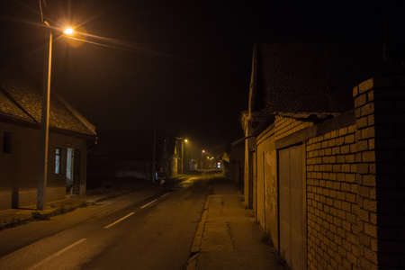 Poorly lit dark street in a rural countryside environment, surrounded by residential houses and orange public lighting, with some empty road, at night. picture of a deserted empty rural dark road, with bad orange public lighting, in a countryside of Europe. Imagens