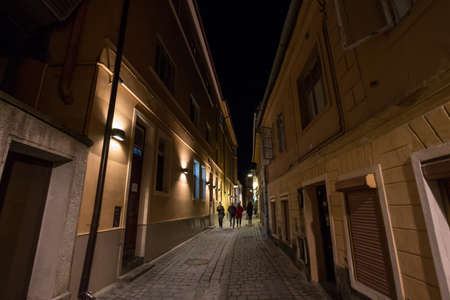 BRASOV, ROMANIA - FEBRUARY 13, 2020: Narrow street of the medieval historical center of Brasov with pedestrians passing by at night. Brasov is a transylvanian historical city. 에디토리얼