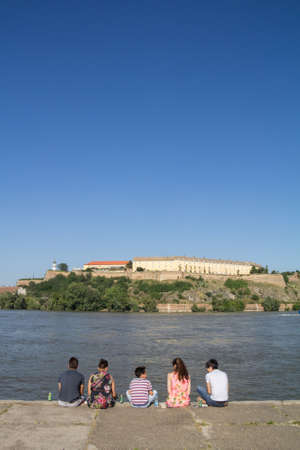 NOVI SAD, SERBIA - JUNE 7, 2015: People sitting together in front of Petrovaradin Fortress in Novi Sad on Danube river, on a sunny summer afternoon. It is the main landmark of the city. Editorial