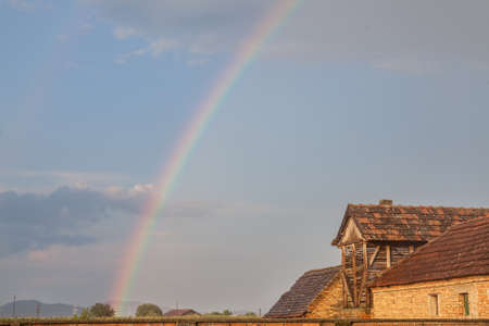 Rainbow in a field of Uljma, in the agricultural region of Banat, province of voivodina, in a field, with a barn in front, after a rain, in a half cloudy half sunny sky. Picture of a rainbow taken in the Serbian village of Uljma, Serbia, with a barn in front and some fields in background.