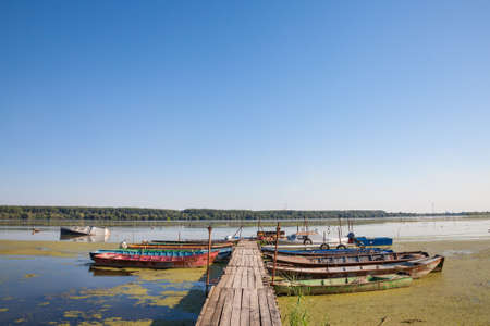 Old boats anchord on a ruined pontoon on the Danube river in Serbia, during a sunny afternoon. The Danube is the biggest river on Central Europe. Panorama of the Danube river in Serbia with an old pontoon on which vintage boats are anchored. The Danube is Europe's second-longest river. It is located in Central and Eastern Europe. Imagens