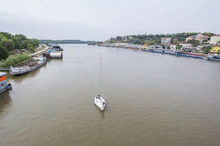 View of Sava river bank in Belgrade with a sailboat in front.