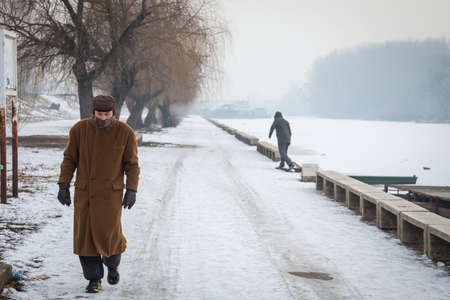 PANCEVO, SERBIA - JANUARY 22, 2017: Old man, senior, walking on the frozen Timis Tamis river during the 2017 winter, in Pancevo.