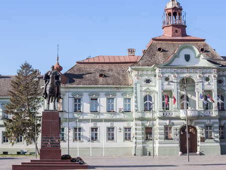 ZRENJANIN, SERBIA - NOVEMBER 23, 2019: Main square with the King Kralj Petar I statue and the city hall, Gradska Kuca, in afternoon. Zrenjanin is one of the main cities of Voivodina. Picture of the main square of Zrenjanin, Serbia, with the city hall and