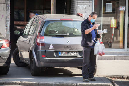 BELGRADE, SERBIA - MAY 9, 2020: Old senior man wearing a respiratory face mask checking the price of his grocieries in the street of Belgrade, during the coronavirus covid 19 health crisis.
