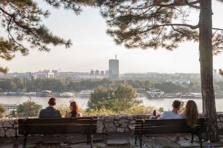 BELGRADE, SERBIA - JULY 11, 2018: Two couples of lovers sitting on benches observing New Belgrade (Novi Beograd) at sunset, with the Usce tower in front, seen from Kalemegdan park. Editorial