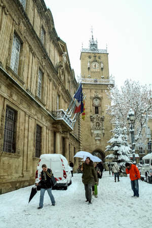 AIX EN PROVENCE, FRANCE - JANUARY 7, 2009: People walking under an unusual snow in front of the Clocktower of Tour de l'Horloge, or clock tower, on the Hotel de Ville (City Hall) Square.
