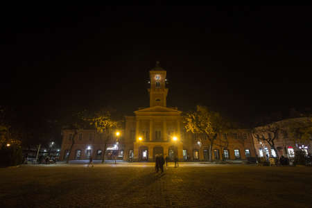 SOMBOR, SERBIA - NOVEMBER 19, 2019: Sombor City Hall, also called gradska kuca, at night, during a foggy evening, with pedestrians passing in speed blur. Sombor is a city of Voivodina. Editorial