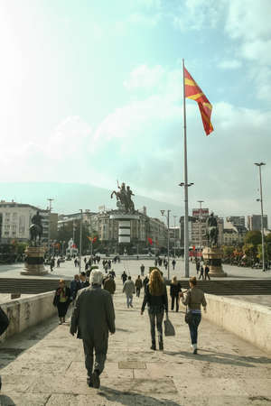 SKOPJE, MACEDONIA - OCTOBER 25, 2011: Crowd of Macedonian people going down the stone bridge to the Alexander the Great statue on Skopje's main square, one of the landmarks of the city.