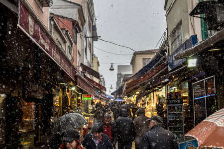 ISTANBUL, TURKEY - DECEMBER 30, 2015: Main street of Kadikoy market, on the Asian side of the city, with restaurants around, crowded, during a snow storm in winter.
