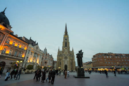 NOVI SAD, SERBIA - NOVEMBER 26, 2016: The Name of Mary Church, Novi Sad catholic cathedral at dusk with a crowd walking on Trg Slobode Square. Editorial