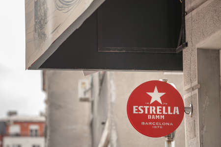 BELGRADE, SERBIA - MAY 3, 2020: Estrella Damm logo in front of a local retailer bar in Belgrade. Editorial