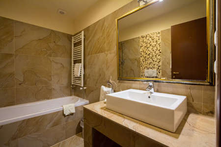 interior of a mid class hotel bathroom with its typical bathtub, a sink with a faucet, some toilet, as well as fresh towers and a large mirror, with a warm light. Picture of the inside of a hotel bathroom in a mid class resort with a bathtub, a faucet, so Editorial