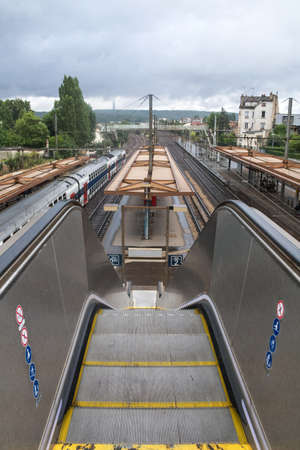 VIROFLAY, FRANCE - JULY 13, 2014: Gare de Viroflay rive gauche train station with a commuter train passing by. It is a suburban railway station on the RER C paris suburb line, in the Yvelines. Éditoriale