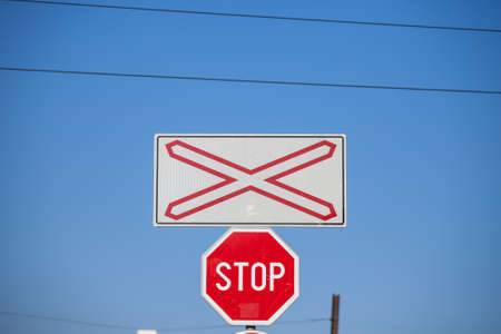 Level crossing sign, called crossbuck, saltire or Saint Andrews cross, standing on a road which crosses a railway track in Pancevo, Serbia, with a standard stop sign. Stock Photo