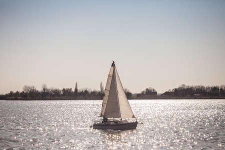 Boat, a sailboat, sailing on the waters of Palic lake, in Subotica, Serbia, during a sunny afternoon. Also known as Palicko Jezero, it is one of the main attractions of Vojvodina province.