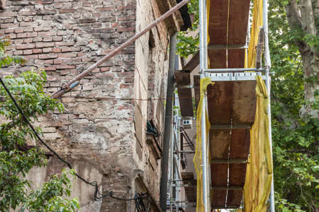 Selective blur on a scaffold in front of a facade of a damaged abandoned house ready to be rebuilt, renovated or demolished. The scaffoldings are protecting people from falling stones.