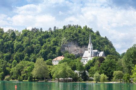 BLED, SLOVENIA - JUNE 12, 2021: Panorama of the Bled lake, Blejsko Jezero, the Saint Martin church, or Cerkev Svetog Martina. it's a catholic church and monument of Slovenia.