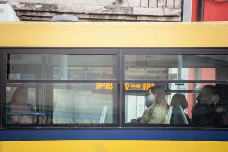 BELGRADE, SERBIA - JUNE 1, 2021: Young woman at the window of a bus from GSP Beograd wearing a respiratory face mask in public transportation during the coronavirus covid 19 health crisis.