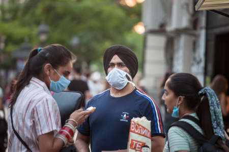 BELGRADE, SERBIA - JULY 6, 2021: Indian tourists, a Sikh male man with its distinctive turban from india, standing in a belgrade street wearing face mask equipment.