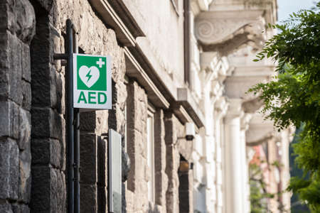 Electric defibrillator logo on a sign in an urban environment, abiding by European standards, indicating the nearby presence of an AED device, an obligation to deal with cardiac diseases and heart attacks.
