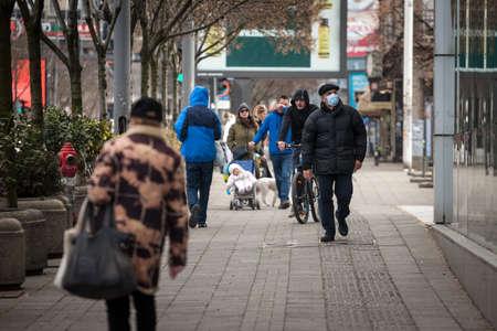 BELGRADE, SERBIA - MARCH 6, 2021: Old senior man wearing a respiratory face mask walking on Kneza Mihaila street in Belgrade in cold winter.