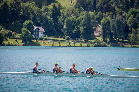 BLED, SLOVENIA - JUNE 13, 2021: Four young male adults, rowers, on a coxed four, a rowing boat, training for rowing for an aviron competition on the Bled lake, in summer, in Slovenia.