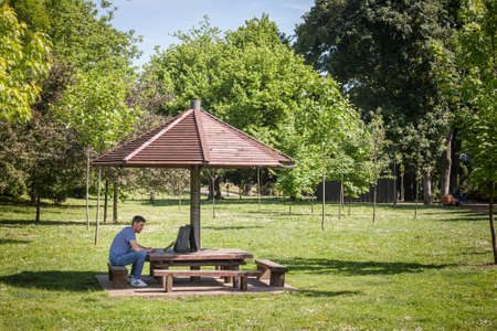 PANCEVO, SERBIA - MAY 22, 2021: Man, online male worker, digital nomad, freelancer, working outsidealone in a park in pancevo, during a sunny afternoon, with his laptop computer. Editorial