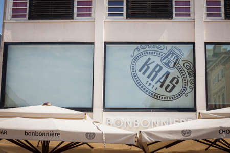 RIJEKA, CROATIA - JUNE 18, 2021: Kras logo in front og their Bonbonniere their shop in Rijeka. Kras is a croatian chocolate and confectionery manufacturer known for its bajadera.