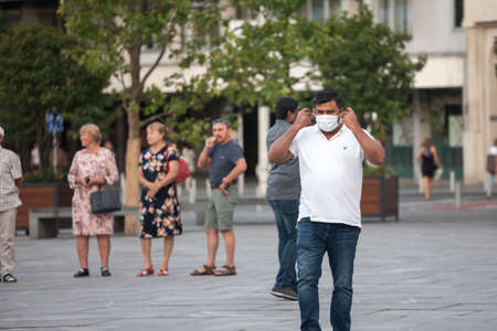 BELGRADE, SERBIA - JULY 22, 2021: Indian tourist, middle aged man from india, touching and adjusting his facemask to remove it in Belgrade streets while traveling.