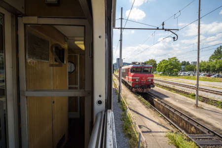 LJUBLJANA, SLOVENIA - JUNE 17, 2021: Slovenian Railways (Slovenske Zeleznice) electric locomotive Series 363 seen from window of 2nd class compartment of passenger on Ljubljana train station.
