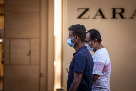 BELGRADE, SERBIA - JULY 30, 2021: Indian tourists, two middle aged male men from india, walking in a belgrade street while traveling in summer, wearing a face mask. Editorial
