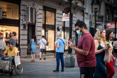 BELGRADE, SERBIA - AUGUST 4, 2021: Indian tourist, young man from india, shooting, filming & taking photos with smartphone in a belgrade street while traveling, wearing a facemask