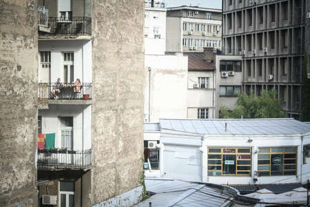 BELGRADE, SERBIA - SEPTEMBER 11, 2014: Selective blur on a young couple, lovers, on a balcony during a warm summer afternoon in a decayed and neglected residential building.