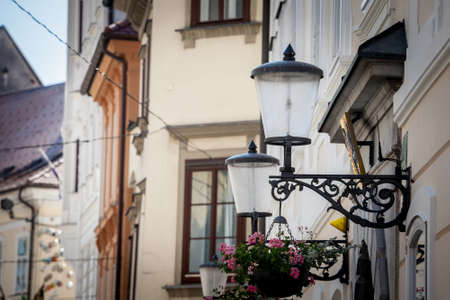 Selective blur on a Vintage old public lamp, typical lantern from the 19th century, on a Street of Ljubljana, a picturesque medieval and narrow street in the historical center of Slovenian capital city.