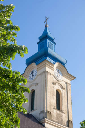 Close up on Church clocktower steeple of the serbian orthodox church of Vlajkovac, Voivodina, Serbia with its iconic clock indicating the time. Vlajkovac is one of the main cities of Serbian Banat.