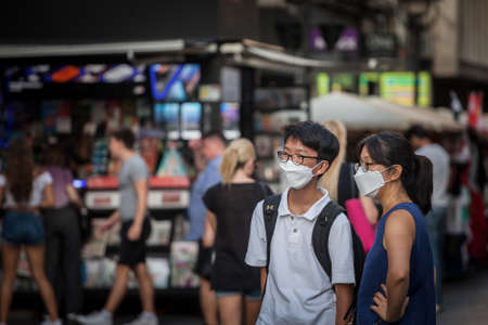 BELGRADE, SERBIA - JUNE 7, 2020: Young Asian couple, lovers, Chinese, wearing a respiratory face mask in the street of Belgrade.