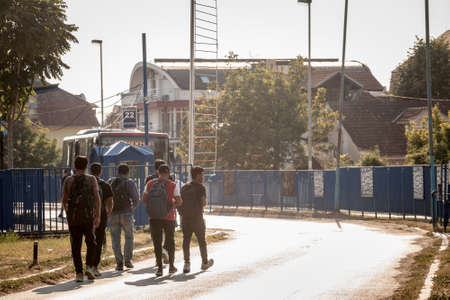 OBRENOVAC, SERBIA - AUGUST 15, 2021: Young afghani refugees from Afghanistan, men, walking to a bus station to take transportation while escaping the afghani conflict, on Balkans Route, on refugees crisis.