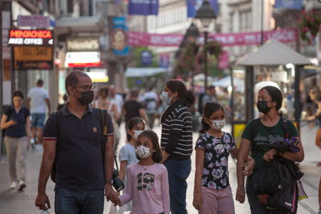 BELGRADE, SERBIA - AUGUST 11, 2021: Indian tourists, a family, mother, father, daughters, surrounded by a crowd in a street, traveling, wearing a facemask on Coronavirus Covid 19 crisis.