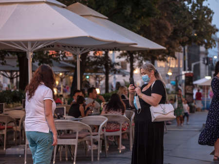 BELGRADE, SERBIA - AUGUST 11, 2021: Selective blur on two women, friends, taking selfies in Belgrade streets at dusk wearing a facemask. Editorial