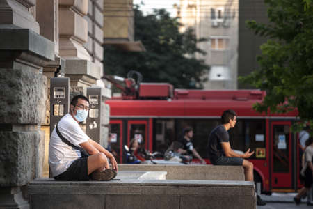 BELGRADE, SERBIA - AUGUST 4, 2021: Young Asian man, Chinese, tourist, wearing a respiratory face mask sitting in the streets of Belgrade.