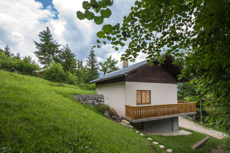 Residential house, a slovenian chalet building, in the middle of a mountain glade, a clearing in the middle of a forest of the julian alps in Slovenia, in Bled. Imagens
