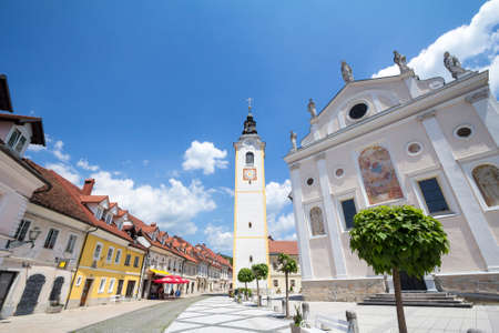 KAMNIK, SLOVENIA - JUNE 16, 2021: Church tower, cerkveni stolp, on the Zupinjska cerkev, a baroque roman catholic church in the center on the main street of the city, Sutna, in a sunny summer afternoon. Editorial