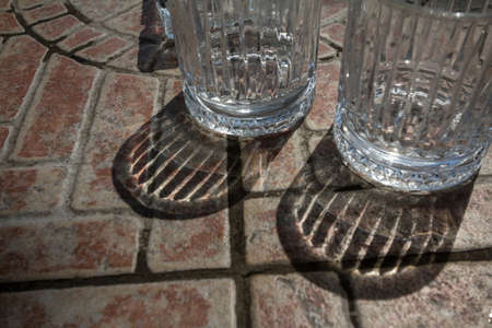 Shadow on a transparent glass, empty, two drinking glasses, with a shade reflection on a restaurant and bar table.