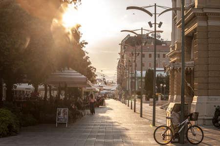 RIJEKA, CROATIA - JUNE 17, 2021: Crowd of people sitting at terraces on Verdijeva ulica, a pedestrian street of the city center of Rijeka, the main city of Istria, during sunset. Editorial