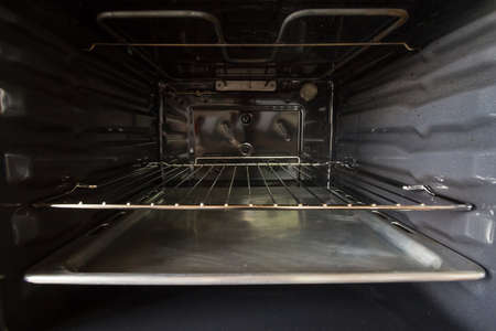 Selective blur on the inside of a built in integrated electric oven, in the interior with it resistance and metal grill, clean, brand new, ready for use as a household appliance for cooking and baking.