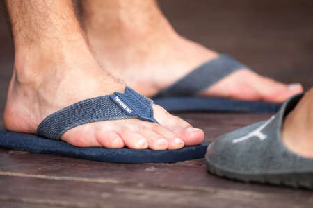 BELGRADE, SERBIA - JULY 31, 2021: Selective blur on a male foot wearing flip flop sandals with the logo of Havaianas. Havaianas is a Brazilian designer and manufacturer of flip flop sandals. Editorial