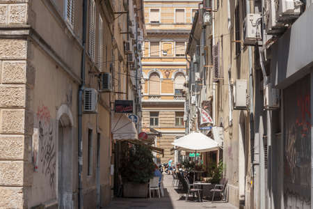 RIJEKA, CROATIA - JULY 18, 2021: Narrow street of stari grad, the old town of Rijeka, with decaying buildings and people having lunch on a terrace of restaurant. Rijeka is a city of istria.
